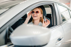 Young woman in sunglasses sitting in new car with key in hand Royalty Free Stock Photography