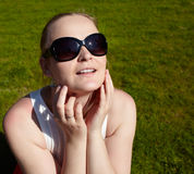 Young woman in sunglasses is sunbathing. Royalty Free Stock Photos