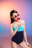 Young woman in sunglasses and swimsuit eating lollipop and looking at camera Stock Image