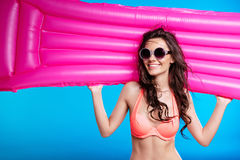 Young woman in sunglasses and swimsuit holding swimming mattress and smiling. Beautiful young woman in sunglasses and swimsuit holding swimming mattress and Royalty Free Stock Images