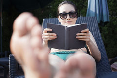 Young woman in sunglasses and a swimsuit relaxing and reading a book Stock Photography