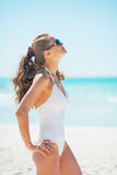 Young woman in sunglasses tanning on beach. Young woman in white swimsuit and sunglasses tanning on beach Stock Photos