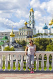Young Woman in Sunglasses with Trinity Sergius Lavra in Sergiev Stock Photography