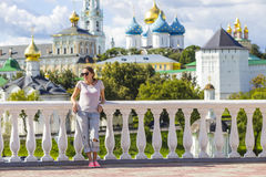 Young Woman in Sunglasses with Trinity Sergius Lavra in Sergiev Stock Photo