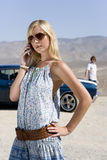 Young woman in sunglasses using mobile phone by car and man in desert Stock Photos