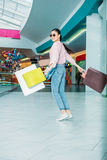 Young woman in sunglasses walking with shopping bags, boutique shopping concept Royalty Free Stock Photo