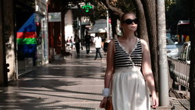 Young woman in sunglasses. Walking under a covered urban arcade in a cool summer dress stock video footage