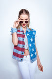 Young woman in sunglasses wearing denim vest with american flag Stock Photography