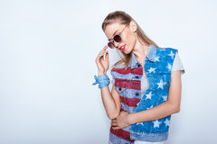 Young woman in sunglasses wearing denim vest with american flag Royalty Free Stock Image