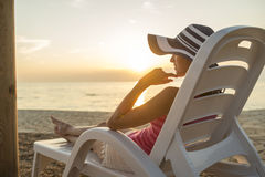 Young woman with sunhat sitting on a plastic beach chair Royalty Free Stock Images