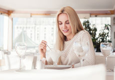 Young woman in sunny restaurant with ice-cream desert Royalty Free Stock Photos
