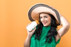 Young woman with sunscreen. On a yellow background royalty free stock photography