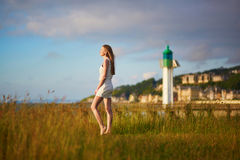 Young woman at sunset on meadow near lighthouse Royalty Free Stock Photo