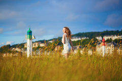 Young woman at sunset on meadow near lighthouse Royalty Free Stock Photos