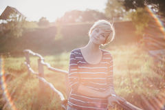 Young woman at the sunset near fence on the country background Royalty Free Stock Photos