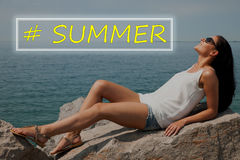 Young woman suntaning on stones on the beach Stock Image