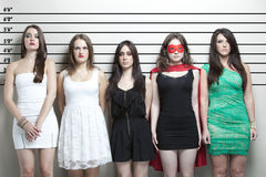 Young woman in superhero costume with friends in a police lineup Stock Images