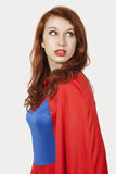 Young woman in superhero costume looking away against gray background Stock Image