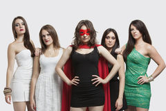 Young woman in superhero costume standing together with friends over gray background Stock Images