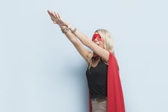Young woman in superhero outfit pretending to leap in the air against light blue background Royalty Free Stock Photography