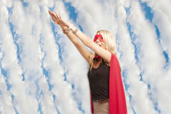 Young woman in superhero outfit taking a leap in the air against cloudy sky royalty free stock images