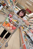 Young woman in the supermarket. To buy food Royalty Free Stock Image