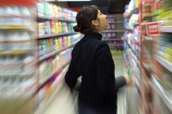 Young woman at supermarket. Pensive young woman at supermarket Royalty Free Stock Photo