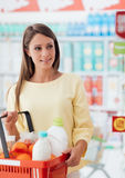 Young woman at the supermarket. Young attractive woman at the supermarket, she is holding a grocery shopping basket and smiling Stock Photos