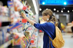 Young woman at supermarket. Beautiful young woman buying food at supermarket Stock Images