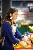 Young woman at supermarket. Beautiful young woman buying vegetables at supermarket Royalty Free Stock Image