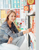 Young woman at the supermarket. Beautiful woman doing grocery shopping at the supermarket, she is taking products on the store shelf Royalty Free Stock Image