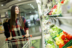 Young woman in supermarket. Young woman buying vegetables in the supermarket Stock Photos