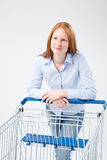Young Woman with Supermarket Cart. A young woman leaning on a supermarket shopping cart and looking away from the camera Royalty Free Stock Images