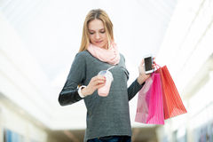 Young woman in supermarket checking time holding shopping bags,. Hustle, busy life. Young woman in a hurry, waiting, checking time on her wristwatch while Royalty Free Stock Images