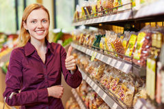 Young woman in supermarket holding. Young smiling woman in supermarket holding her thumbs up Stock Photo