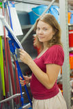 A young woman in a supermarket. Image of a young woman who chooses a ladle in the supermarket Royalty Free Stock Photo