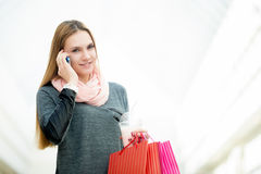 Young woman in supermarket making a call. Smiling young woman talking on cellphone while holding paper bags and strawberry cocktail in shopping center, copyspace Royalty Free Stock Photos