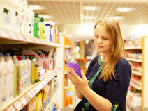 Young woman in the supermarket reading inscription. Young blonde woman is reading inscription on the cleaner bottle in the supermarket Stock Photography