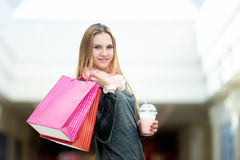 Young woman in supermarket with shopping bags and strawberry coc. Smiling teenage girl happy with her purchases in shopping mall, holding paper bags and Royalty Free Stock Photo
