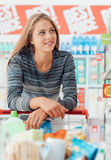 Young woman at the supermarket. Young smiling woman at the supermarket, she is shopping and pushing a cart along the store aisles Royalty Free Stock Photo