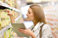 Young woman in supermarket using tablet. Woman in supermarket checking shopping list on tablet Royalty Free Stock Images