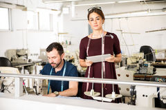 Young woman supervising some workers. Portrait of a good looking female supervisor looking at the work of a tailor in a textile factory Royalty Free Stock Photos