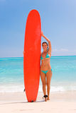 Young woman with surfboard. Smiling young woman in bikini with long red surfboard on tropical beach, sea in background Royalty Free Stock Photography