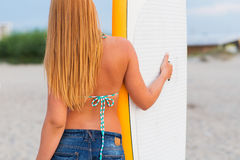 Young woman with surfboard on beach Stock Photo
