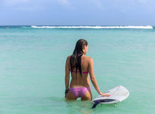 Young woman with surfboard in ocean Stock Photo