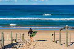 Young woman with surfboard walking on the sandy beach Royalty Free Stock Photos