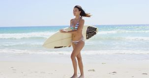 Young woman surfer striding along a tropical beach. Carrying her surfboard under her arm at the edge of the ocean stock footage