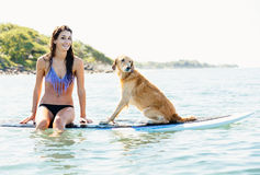 Young Woman Surfing with Her Dog Royalty Free Stock Photography