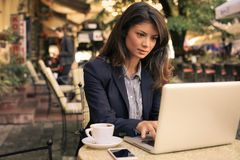 Young woman surfing internet on laptop at cafe. Business woman Stock Image