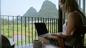 Woman Using Laptop. Young woman surfing on internet outside the house on the terrace with a view over Guiling mountain landscape in Yangshuo County,China stock video